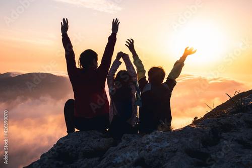 Obraz Madre e hijos disfrutando del atardecer desde lo más alto. Concepto de superación y éxito.  - fototapety do salonu
