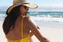 Mixed Race Woman On Beach Holiday Using Sunscreen Cream