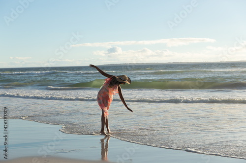 Mixed race woman wearing straw hat walking along the seashore with spread hands