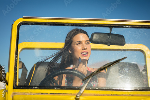 Happy caucasian woman sitting in beach buggy by the sea putting on lipstick