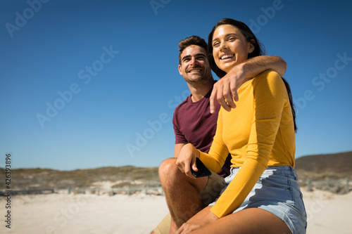 Happy caucasian couple on the beach embracing woman holding smartphone