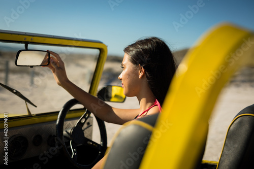 Happy caucasian woman sitting in beach buggy by the sea looking at herself in car mirror