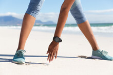 Low Section Of Mixed Race Woman Exercising On Beach Wearing Smartwatch Stretching
