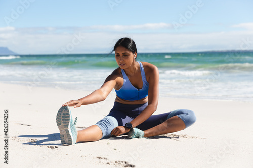 Mixed race woman exercising on beach wearing wireless earphones sitting and stretching