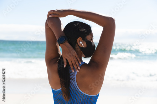 Mixed race woman exercising on beach wearing face mask and wireless earphones stretching arms