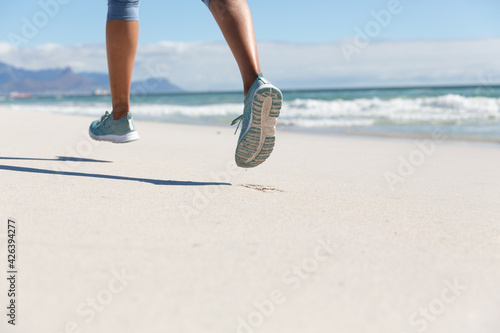 Low section of mixed race woman exercising on beach running