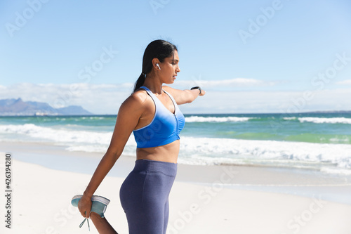 Mixed race woman exercising on beach wearing wireless earphones stretching