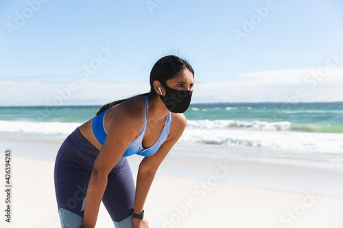 Mixed race woman exercising on beach wearing face mask and wireless earphones taking rest