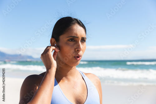 Mixed race woman exercising on beach putting on wireless earphones