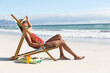 Leinwandbild Motiv Mixed race woman on beach holiday sitting in deckchair sunbathing