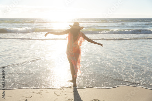 Mixed race woman on beach holiday relaxing walking at sunset