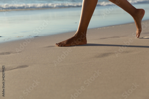 Low section of mixed race woman on beach practicing yoga durning sunset