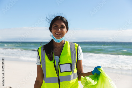 Portrait of smiling mixed race woman wearing face mask collecting rubbish from the beach