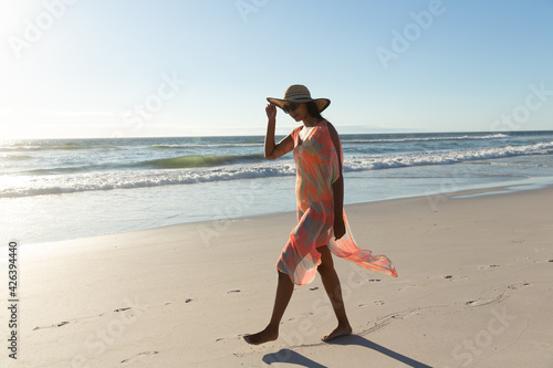 Happy mixed race woman on beach holiday walking