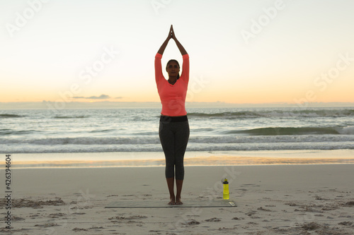 Mixed race woman on beach practicing yoga during sunset