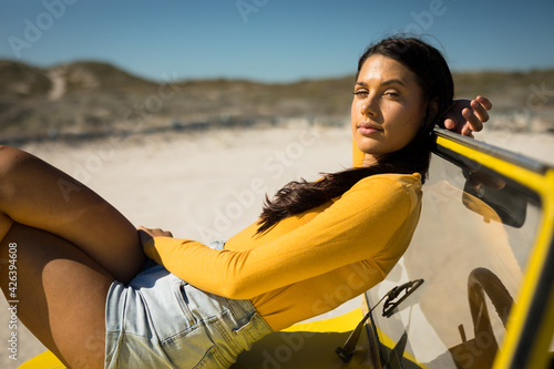 Caucasian woman lying on a beach buggy looking to camera
