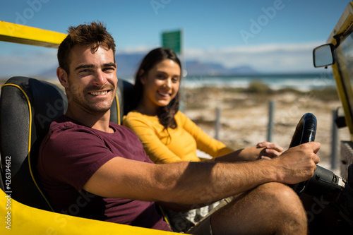 Portraits of happy caucasian couple looking to camera sitting in beach buggy by the sea talking