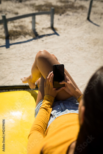 Midsection of caucasian woman lying on a beach buggy by the sea using smartphone