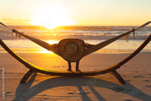 Mixed race woman on beach holiday lying in hammock during sunset