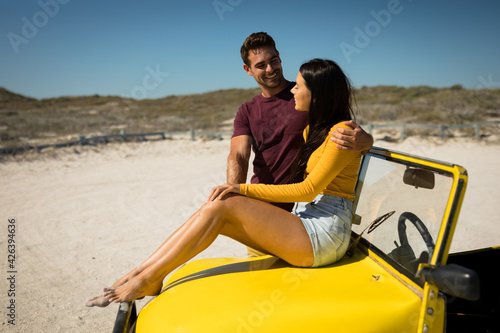 Happy caucasian couple by the sea smiling to each other, woman sitting on beach buggy