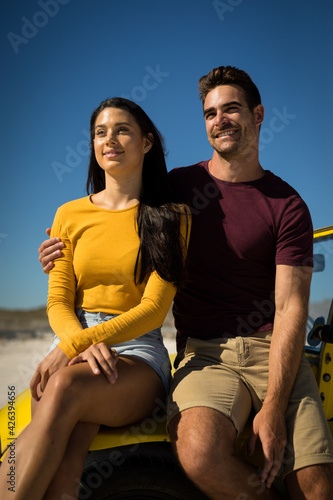 Happy caucasian couple woman sitting in beach buggy by the sea both looking ahead