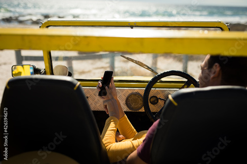 Caucasian couple lying on a beach buggy by the sea using smartphone