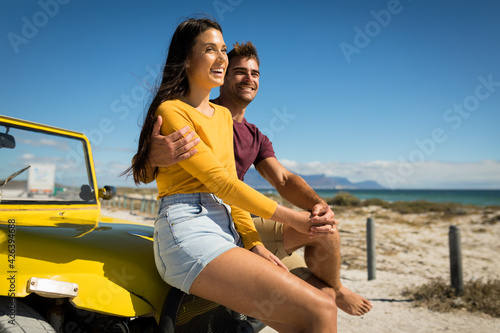 Happy caucasian couple sitting on beach buggy by the sea holding hands