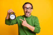 Photo Of Excited Man Hold Alarm Clock Open Mouth Direct Finger Wear Eyewear Green Sweater Isolated Yellow Color Background