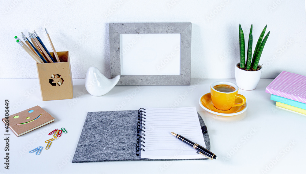 Fototapeta Workspace home office. Cozy home office on white table , fountain pen,  yellow cup of coffee, frame with space for tekst, notebook Background with copy space. Elegant feminine workspace.