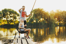 Young Happy Couple Is Fishing On The Pier At The Lake At Sunset