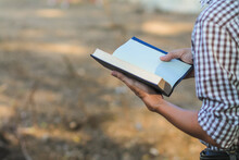 A Young Man Holding A Bible Opened For Learning To Understand The Bible In Order To Pray To God And To Ask God To Protect Himself And His Family. The Concept Of Bible Learning And Faith In God
