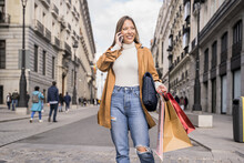 Cheerful Hispanic Woman Holding Shopping Bags And Talking On The Phone In Madrid, Spain