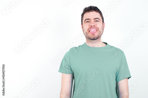 young handsome caucasian man wearing green t-shirt against white background with happy and funny face smiling and showing tongue Wallpaper Mural