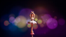A Ballerina Figurine With Colorful Modern Bokeh Background.