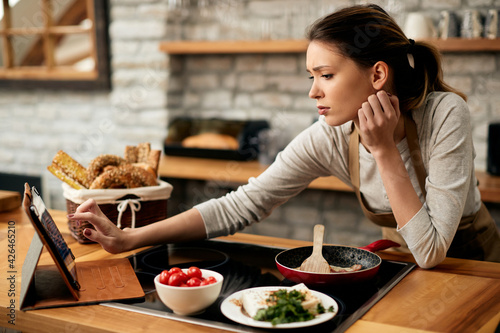 Canvas Young woman looking for recipe on digital tablet while making breakfast at home
