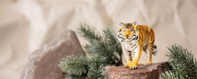Tiger Symbol Of The Chinese New Year 2022. Figurine Of Tiger On Stone With Branches Spruce Tree On Pastel Background. Copy Space. Banner
