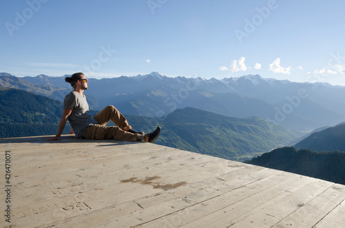 Canvas Print Young man sits on the observation deck at the top of the mountain