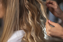 Closeup Shot Of Hairstylist Hands Makes Curls