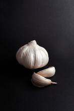 Still Life Of Garlic Heads And Garlic Cloves On Black Background.  Healthy Ingredients Food Concept.