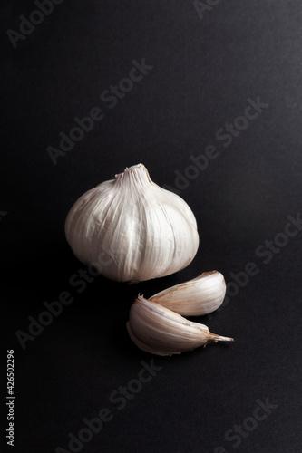 Fotografiet still life of garlic heads and garlic cloves on black background