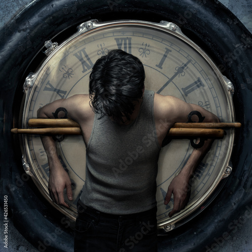 Fotografia drummer hanging on a clock with drum sticks