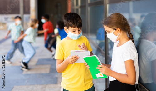 Fototapeta Portrait of primary school girl and boy wearing protective face masks talking outside before lesson, new normal during coronavirus pandemic situation obraz