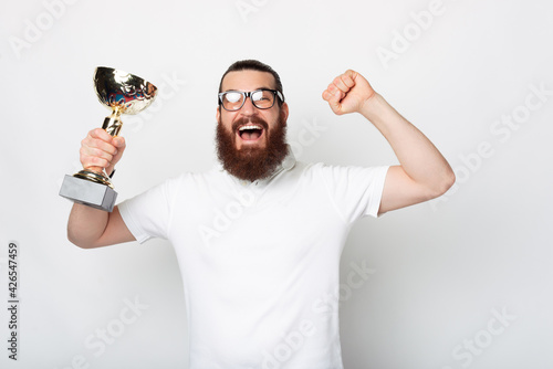 Canvas Amazed bearded hipster man in white t-shirt celebrating and holding champion cup