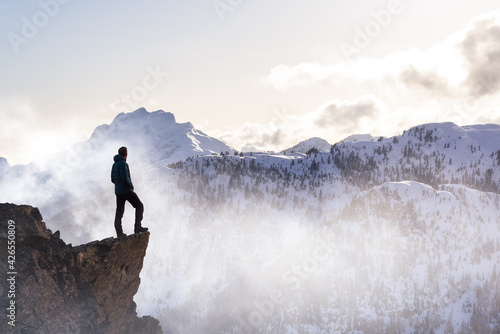 Photo Fantasy Adventure Composite with a Man on top of a Mountain Cliff with Dramatic Landscape in Background during Sunset or Sunrise