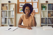 Leinwandbild Motiv Video or online lesson. African american woman waving hello smiling looking at camera sitting at office desk. Excited businesswoman teacher lecturer recording educational webinar, greeting students