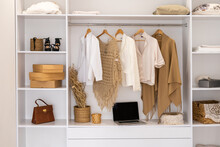 Basic Women's Clothes On A Hanger And Blurred Notebook , Open Wardrobe With Textile Curtains Close-up
