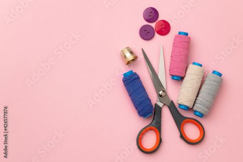 Fototapeta Multicolored thread spools and buttons on pink background