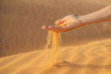 Desert, Sand Puffs Through The Fingers Of A Mans Hand