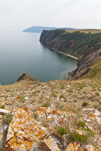 Baikal Lake on a summer day. Steep coast of Olkhon Island with rocks covered with red lichens