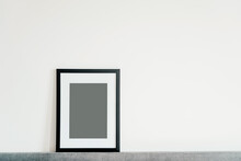Blank Wooden Photo Frame Stands In The Interior On A White Background. Mockup Poster Frame.